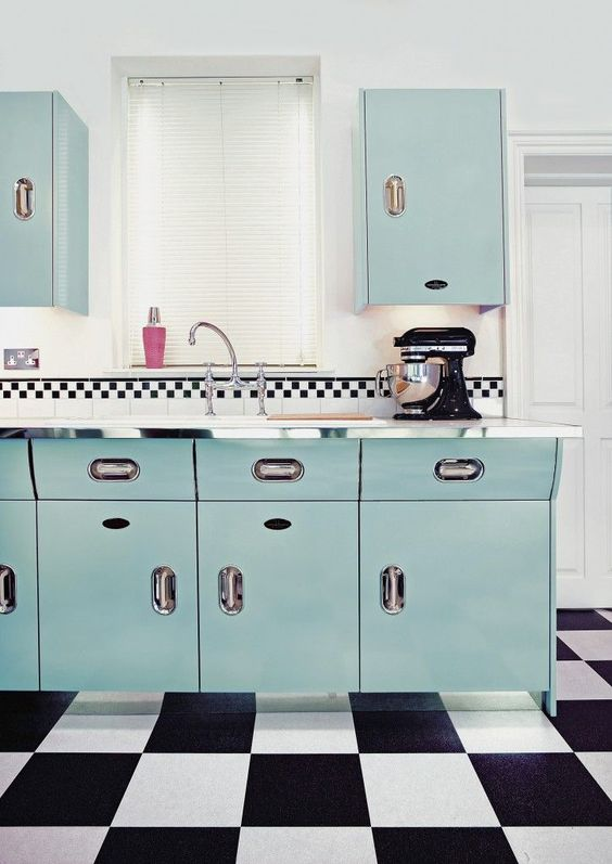 a gorgeous blue kitchen with a black and white tile floor looks really retro thanks to colors and tiles