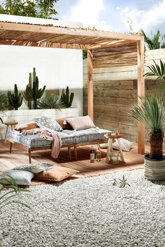 a simple and welcoming wooden daybed with a comfy mattress and pillow placed in a cabana to avoid sunlight