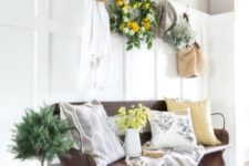 19 a potted plant in a bucket, a greenery and citrus wreath, yellow blooms and botanical print pillows for summer vibes
