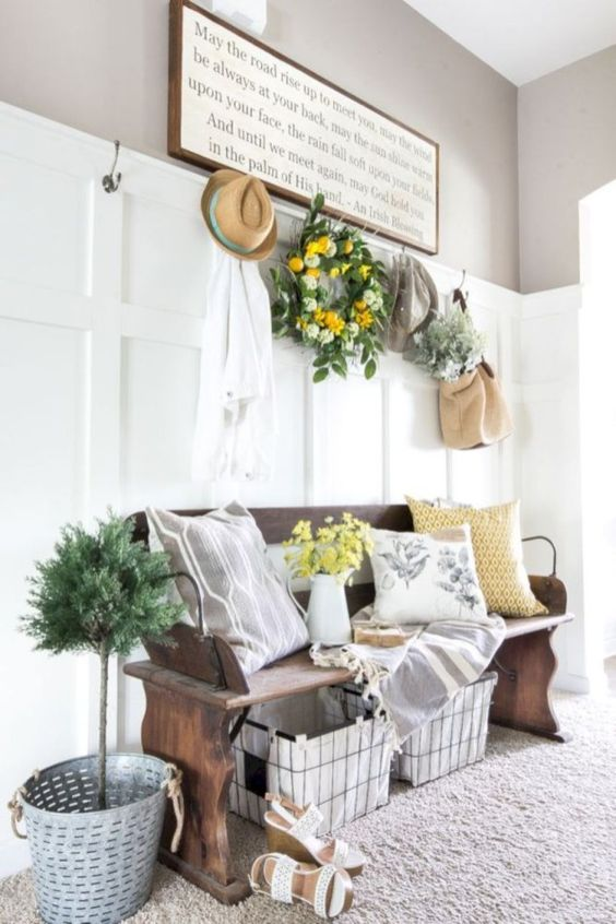 a potted plant in a bucket, a greenery and citrus wreath, yellow blooms and botanical print pillows for summer vibes