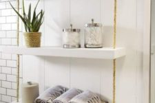 19 a simple and smart bathroom hanging shelf with thick white shelves and ropes can be easily DIYed
