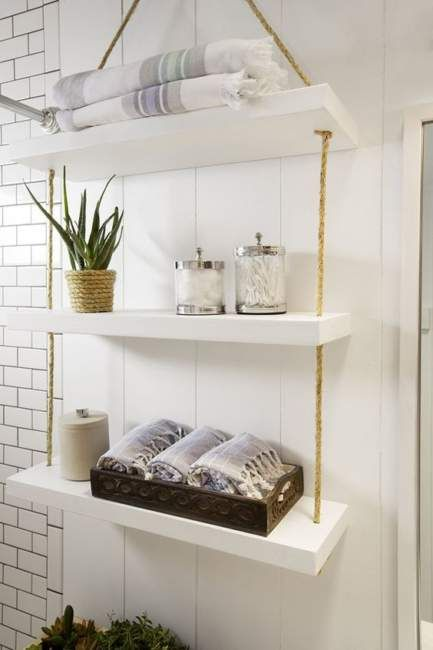 a simple and smart bathroom hanging shelf with thick white shelves and ropes can be easily DIYed