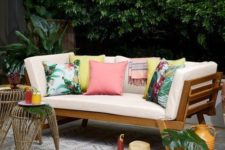 19 a simple modern wooden daybed with colorful pillows that give it a tropical feel and make it brighter