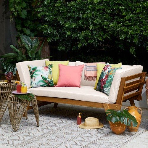 a simple modern wooden daybed with colorful pillows that give it a tropical feel and make it brighter