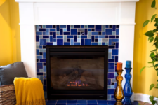 20 a fireplace clad with bright mosaic blue tiles continues the yellow and blue color scheme of the space