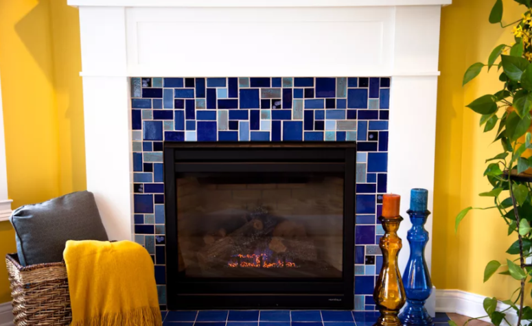 a fireplace clad with bright mosaic blue tiles continues the yellow and blue color scheme of the space