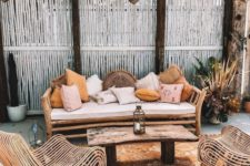 20 a simple rattan daybed with lots of muted color pillows is the main piece in this boho terrace