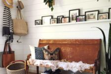 20 a summer boho entryway with potted greenery, a bench with printed pillows, baskets for storage and wicker elements