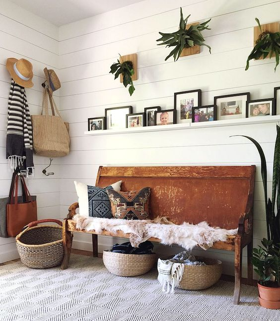 a summer boho entryway with potted greenery, a bench with printed pillows, baskets for storage and wicker elements