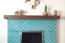 21 a rustic fireplace with a wooden mantel is spruced up with turquoise fish scale tiles to create an optical illusion and make a statement with color