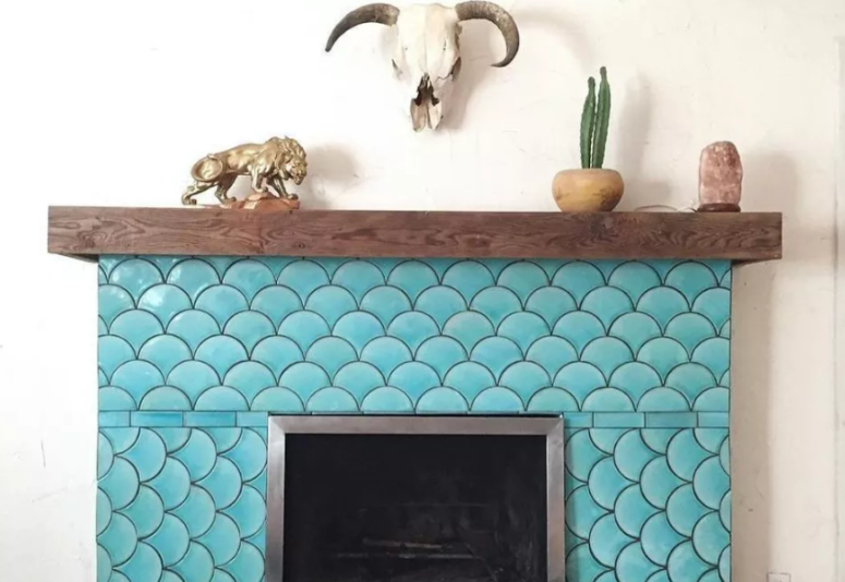 a rustic fireplace with a wooden mantel is spruced up with turquoise fish scale tiles to create an optical illusion and make a statement with color