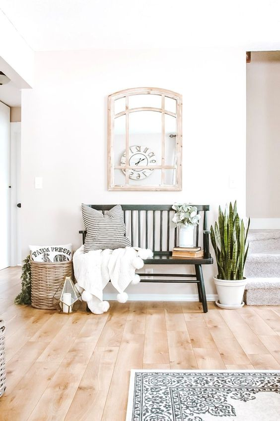 a summer farmhouse entryway with a succulent in a pot, a basket with greenery, a candle lantern, a bench and a pompom blanket