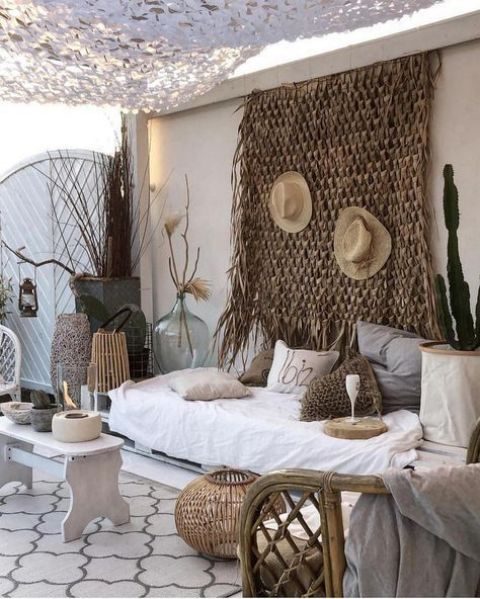 a whitewashed pallet daybed with lots of crochet pillows is the centerpiece of this desert-inspired boho outdoor space