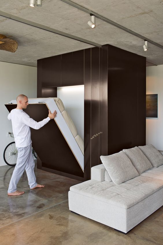 an industrial loft with a metal cube, which hides a Murphy bed, means no compromise on style and decor