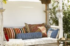 22 a whitewashed wooden daybed with a roof over it and lot sof colorful pillows is a gorgeous boho place to have a siesta