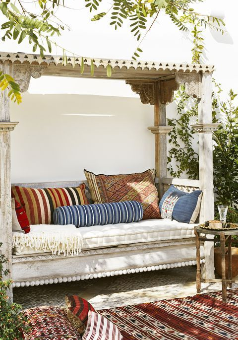 a whitewashed wooden daybed with a roof over it and lot sof colorful pillows is a gorgeous boho place to have a siesta