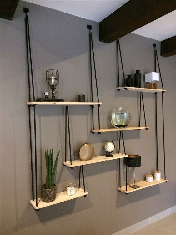 a whole hanging shelving unit with several shelves and black ropes looks very contrasting and will fit any boho room