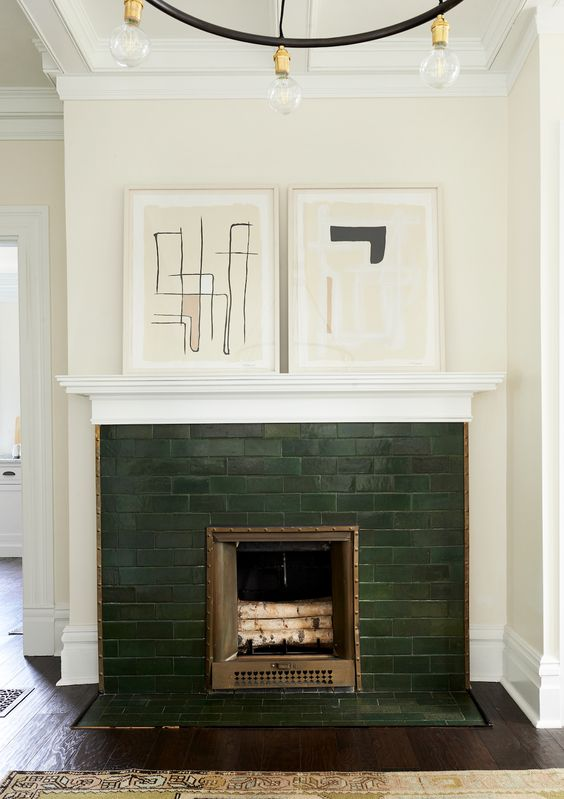 accent your small fireplace with dark green tiles and abstract artworks on the mantel if your home is mid-century modern or contemporary