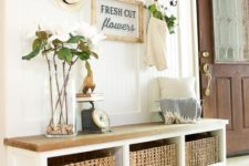 22 an oar, a sign, blooms and woven drawers create a light summer feel in the entryway and a striped rug helps on that