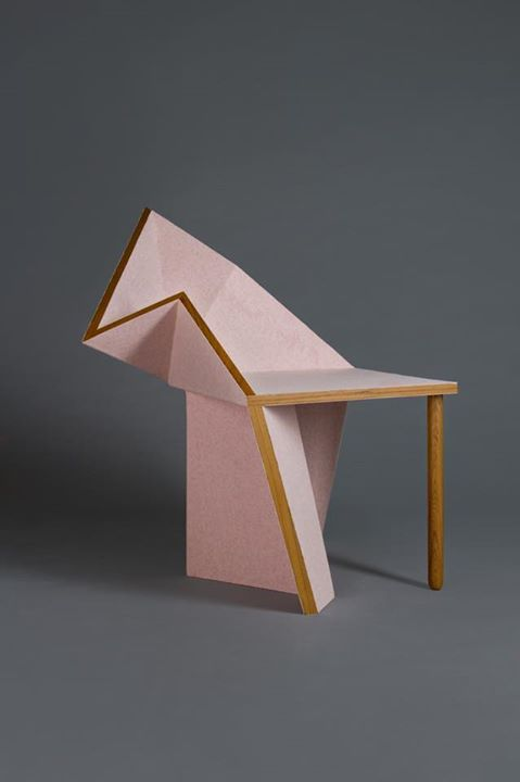 a unique pink geometric chair with a single leg and a solid base, which is shaped sculpturally
