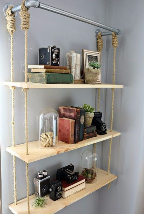 an industrial pipe with a hanging shelving unit with thin plywood tiers and ropes is a cool idea for an industrial space