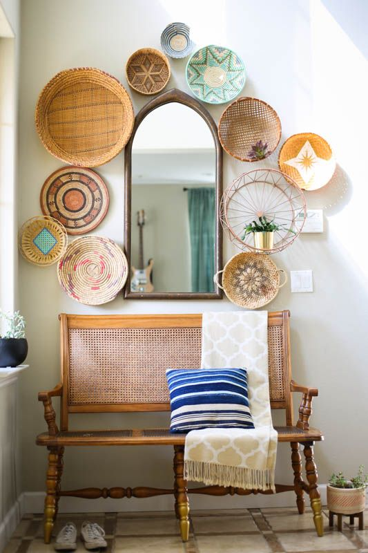 give your entryway a bold summer feel with a wall of decorative baskets - painted and printed ones and a striped pillow