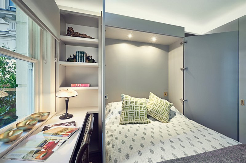 a home office with a hidden Murphy bed behind the doors lets the space double as a bedroom and home office