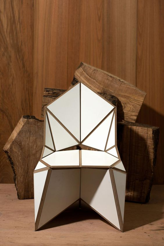 a white geometric and sculptural chair with gold touches looks very futuristic and super bold