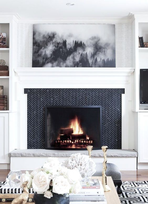 if you have a monochromatic space, clad your fireplace with black tiles in a herringbone pattern and add stone for a chic look