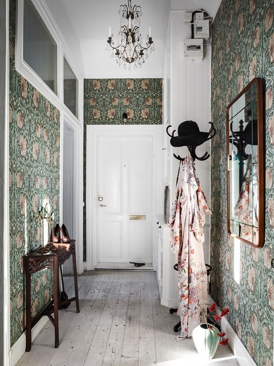 moody green floral wallpaper covering all the walls takes over the whole space and makes it cooler