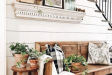 24 potted greenery, an artwork and a botanical print pillow instantly create a summer feel in the entryway
