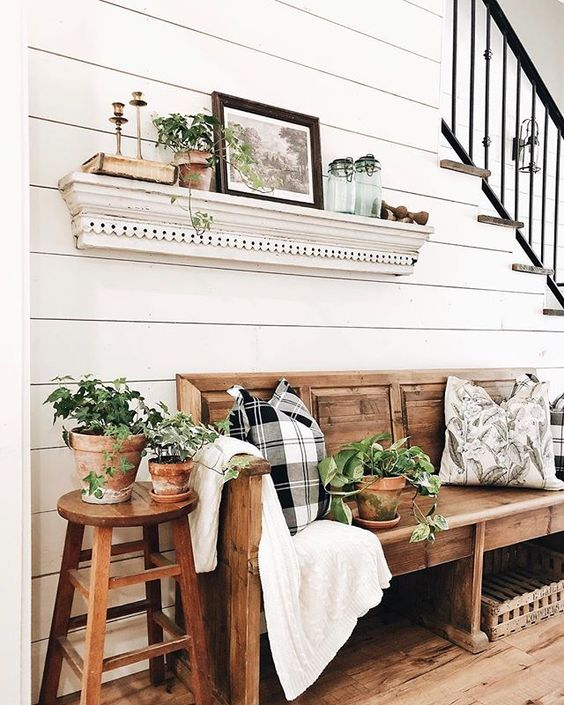 potted greenery, an artwork and a botanical print pillow instantly create a summer feel in the entryway