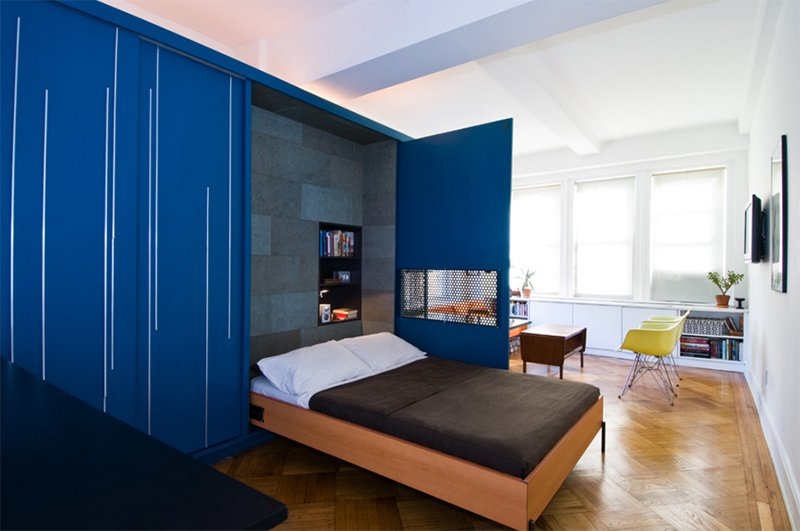 a Murphy bed integrated between the living room and the kitchen behind the bold blue doors