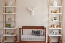 25 shelving units hanging on ropes with tassels on both sides of the crib is a cool idea that brings a relaxed feel to the space
