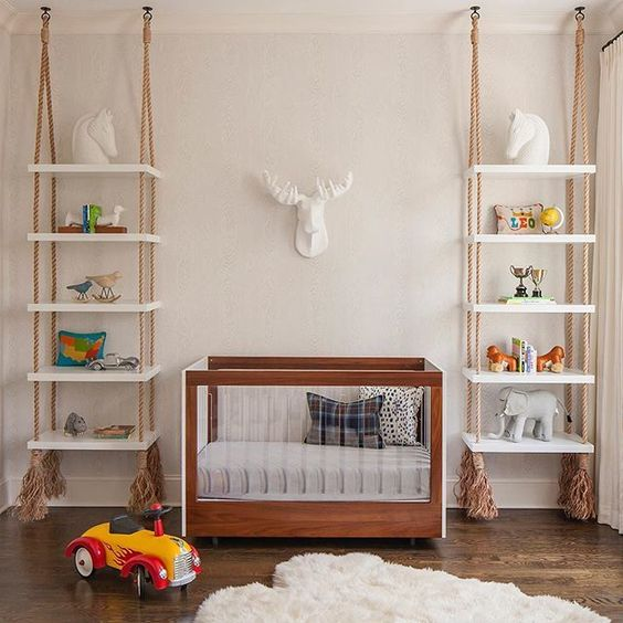 shelving units hanging on ropes with tassels on both sides of the crib is a cool idea that brings a relaxed feel to the space
