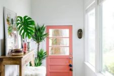25 summer vibes are achieved with a pink door, a bright boho rug, potted palms and a bold artwork