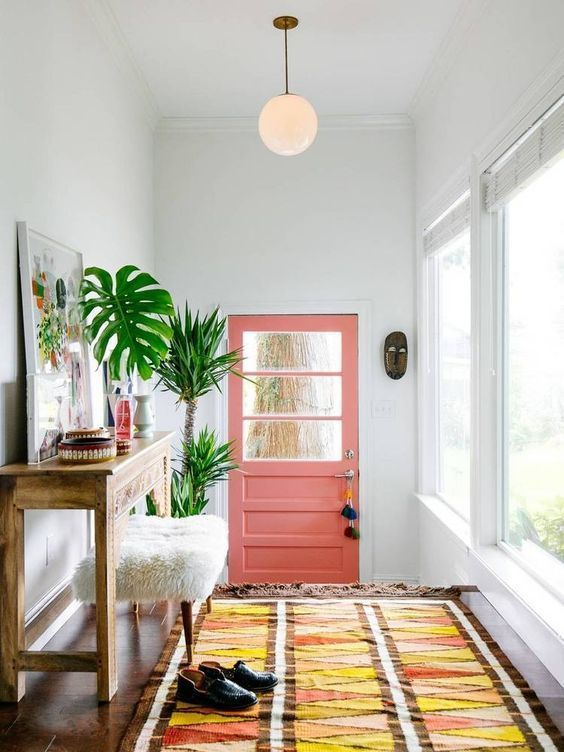 summer vibes are achieved with a pink door, a bright boho rug, potted palms and a bold artwork
