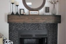 25 tiny glossy black tiles around the fireplace and a dark stained mantel make the fireplace zone cooler and bolder
