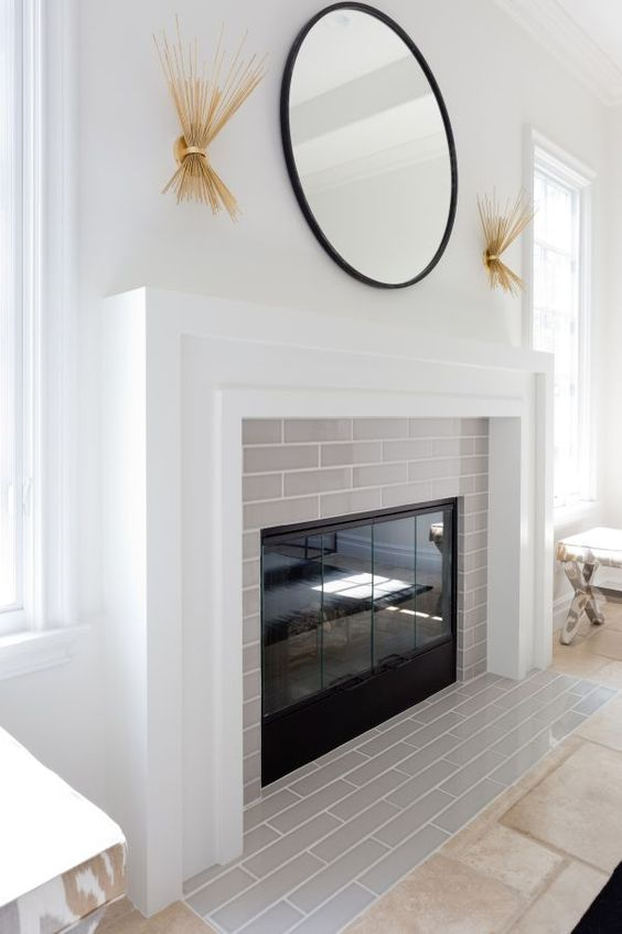 a clean and fresh idea of cladding your fireplace with thin light grey tiles and a white mantel covering the whole piece