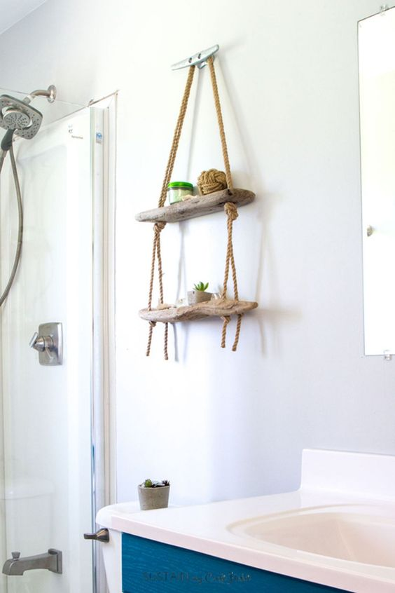 a small hanging display shelf for a bathroom made of driftwood and ropes will add decorative value to the space