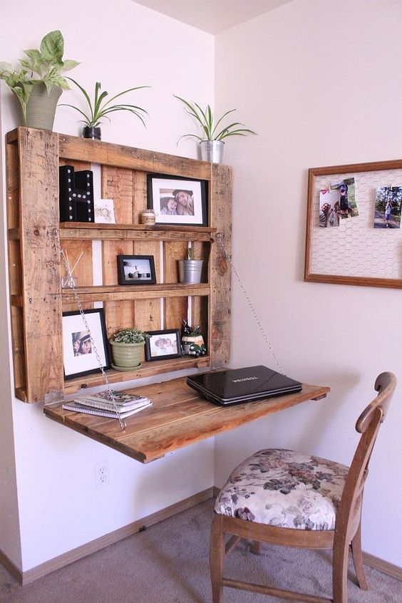 a DIY rustic Murphy desk made of a stainned pallet and chains that hold the desktop in a very secure way and with display space