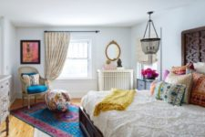 a bright eclectic bedroom done with colorful printed textiles, a modern wooden bed, a boho chandelier and some carved dressers
