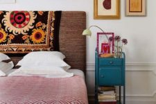 a bright eclectic bedroom with an upholstered bed, a wooden chest, a bight vintage nightstand and abstract art