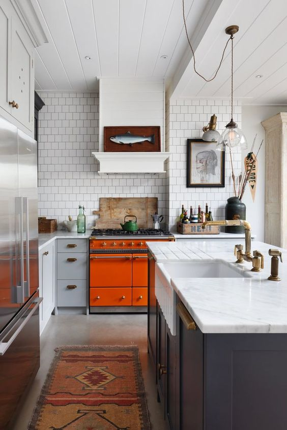 a bright eclectic kitchen with an orange cooker, navy and grey cabinets, white stone countertops and catchy artworks