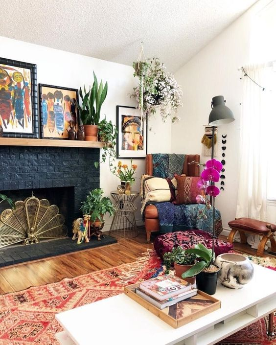 a bright eclectic living room with folksy rugs and blankets, potted greenery and blooms, lamps and bold artworks