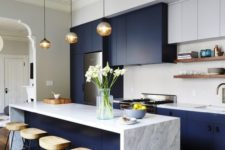 a bright navy and white galley kitchen with a stone countertop, pendant lamps, wooden stools and a white tile backsplash