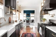 a chic black galley kitchen with white countertops and brass touches plus a printed rug and vintage pendant lamps