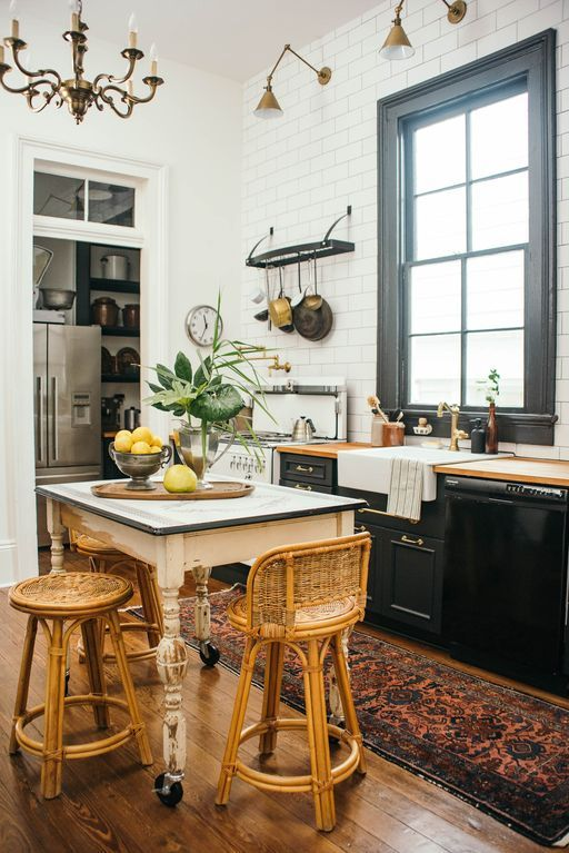a chic kitchen pairing black cabinets with neutral countertops, a shabby chic table, vintage rattan chairs and industrial lamps