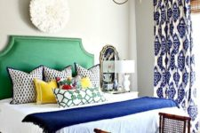a colorful eclectic bedroom in bold blue and emerald green, with a mix of prints and vintage touches