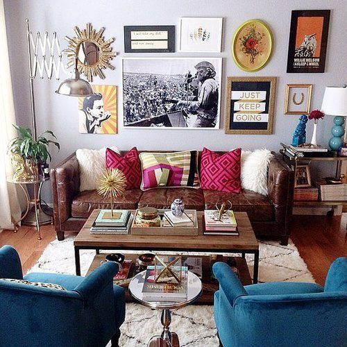 a colorful eclectic living area with a crazy gallery wall, velvet and leather furniture, an industrial coffee table